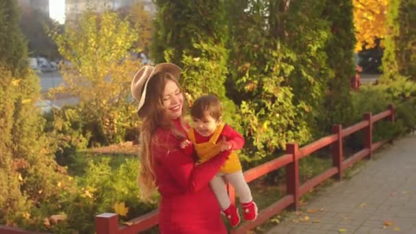 Mother and little daughter playing together in a park. Autumn time.