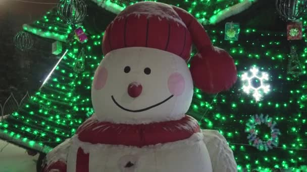 Funny snowman on the background of Christmas tree, night time, closeup.