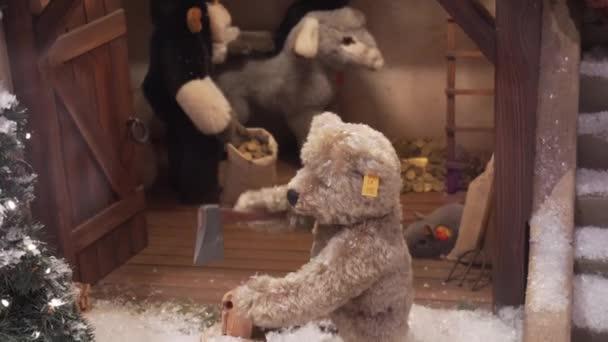 MUNICH, GERMANY - NOV 20, 2018: A mechanical toy bear cuts a log, a monkey strokes a donkey. Christmas toys, a large storefront.