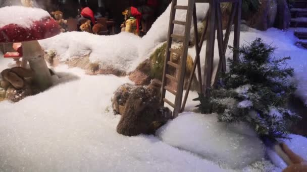 München, Deutschland - 20.11.2018: Der Spielzeugbär auf dem Aussichtsturm betrachtet das mechanische Schwein. Weihnachtsgeschäft Schaufenster Einkaufszentrum.