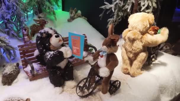 München, Deutschland - 20.11.2018: Der mechanische Spielzeughase dreht am Lenkrad eines Fahrrads. ein Plüschhund mit einem Buch auf einer Bank, neben zwei Spielzeugbären.