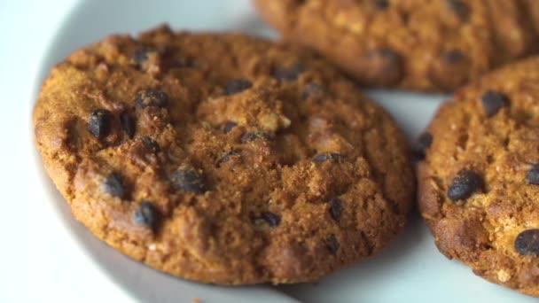 Chutné sušenky s kousky čokolády mělké zblízka. Čokoládový dort sušenky na bílém keramickém talíři na dřevěném stole.Ruka vzít sušenky s čokoládovým zpomalením 4K