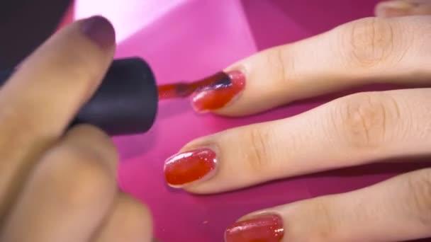 Specialista pokrývá nehty klienta červeným lakem. Zavřít
