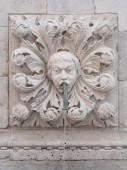 Closeup photograph of an old historic fountain caricature face of a child with floral decorative surrounding protruding from a white masonry stone wall in Dubrovnik Croatia.
