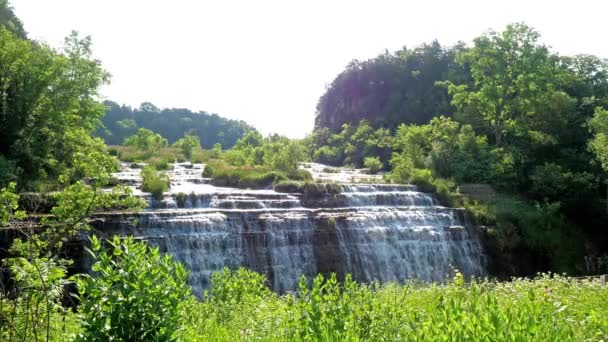 View of the beautiful Thunder Bay Waterfall with water pouring over the rocky stepped cliff and tall grasses and wildflowers swaying in the breeze along a road in Galena Illinois.