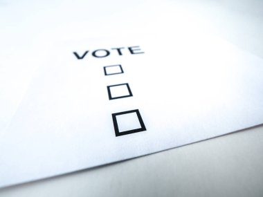 A closeup photograph of a blank generic vote ballot on white paper and white background.