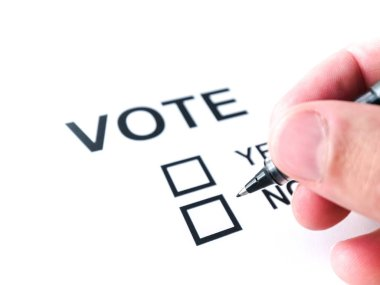 A background image of a male white Caucasian man's hand holding a pen ready to check a box on a generic vote ballot with a white background.