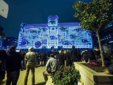 Chicago, IL - September 29th, 2018: Crowds of people watch light displays at the grand opening of Art on theMart, the longest running digital art display in the world in downtown Saturday Night.