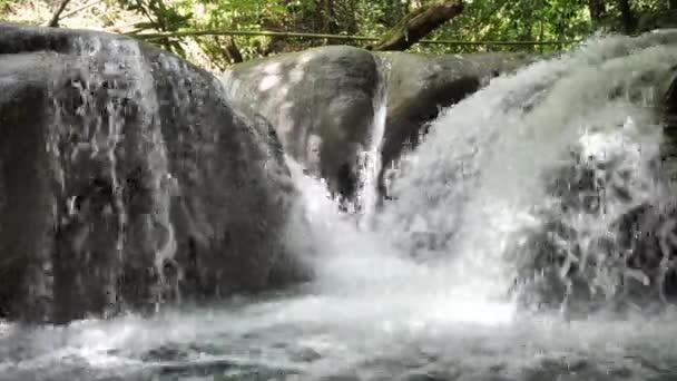 Nahaufnahme des Wasserfalls mit dem Spitznamen Waschmaschine, während sich Wildwasserströme über die runden Kalksteinfelsen des Mayfield Falls River auf der tropischen Insel Jamaica ergießen.