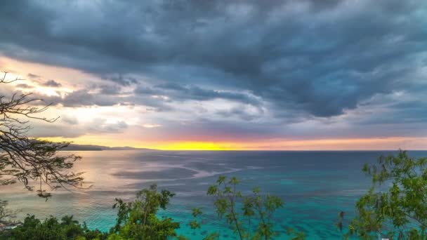 A gorgeous sunset timelapse with dramatic clouds with blue, pink, orange and yellow colors moving across the sky over the Atlantic Ocean in Jamaica with beautiful tropical blue water framed by trees.