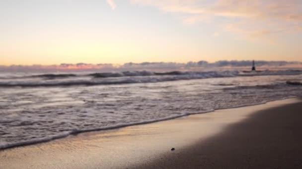 Nem fókuszált háttér lövés hullámok gördülő egy homokos tengerparton egy színes rózsaszín lila és kék napkelte ég tükröződik a nedves homok és a víz.