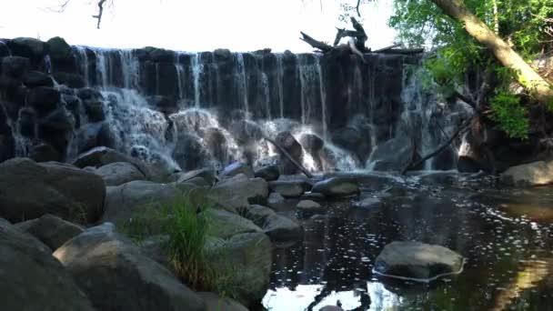 Stacionární záběr vody kaskádovitě stékající po skalnatém vodopádu do řeky dole s balvany v popředí a bílými bublinami, tvořícími se na hladině vody, jak teče po proudu.