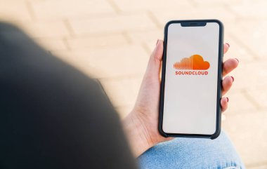 BERLIN, GERMANY AUGUST 2019: Woman hand holding iphone Xs opening soundcloud Music streaming app in the city. Streaming music via the Internet