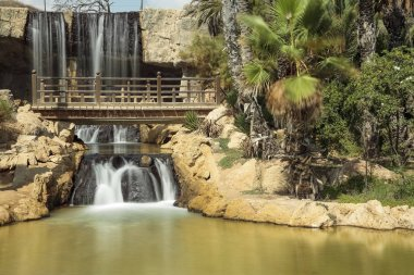 horizontal view of cascade and lake of el palmeral park in the city of alicante, spain
