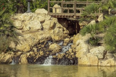 horizontal view of a little cascade and wooden bridge in El palmeral park on a sunny day in the city of alicante, spain