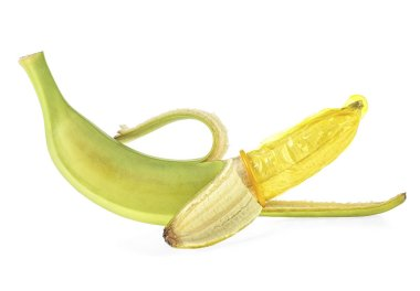 Green banana and yellow condom on white background