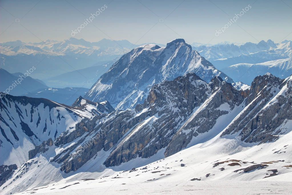 Snowy rock walls of Wettersteingebirge and Hohe Munde peak of Mieminger Kette range in Northern Limestone Alps in German Austrian border, in background Zillertaler and Stubaier Alpen ranges in Tirol