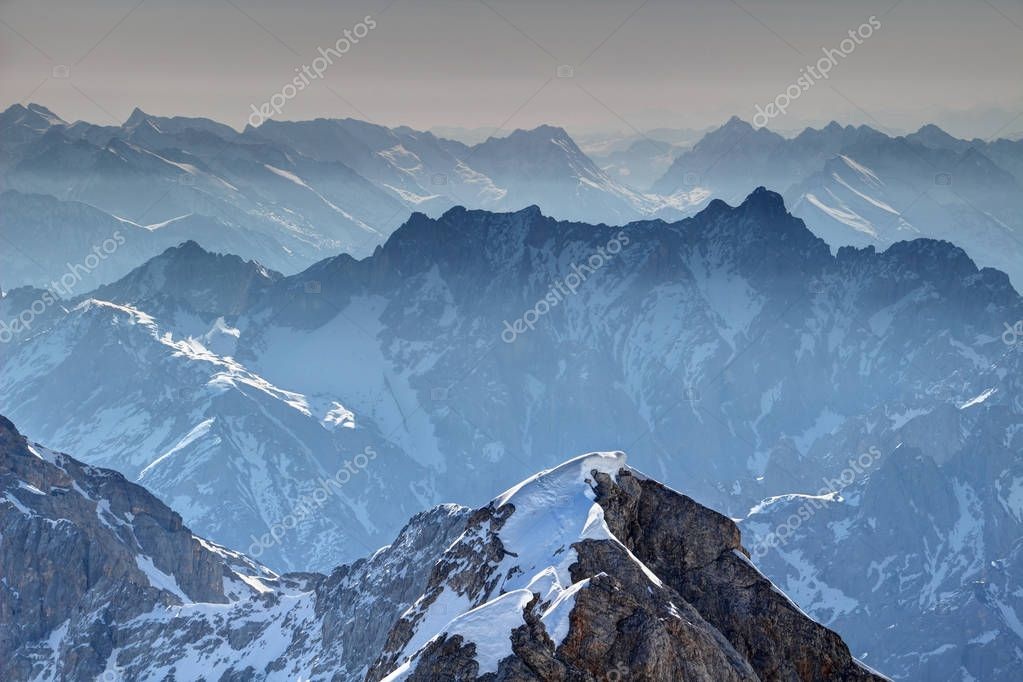 Jagged blue ridges of Jubilaumsgrat and Dreitorspitze in morning mist in snowy Wettersteingebirge range with Karwendel mountains in background, Zugspitze Northern Limestone Alps Bayern Germany Europe