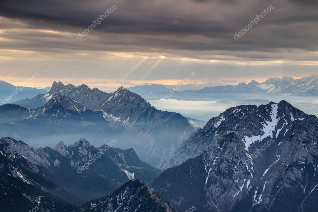 Sun rays burst through dark grey cloud cover over misty jagged Koschutnikturm Kosutnikov Turn peaks of Koschuta Kosuta ridge in Karawanken Karavanke range in autumn morning, Austria / Slovenia Europe