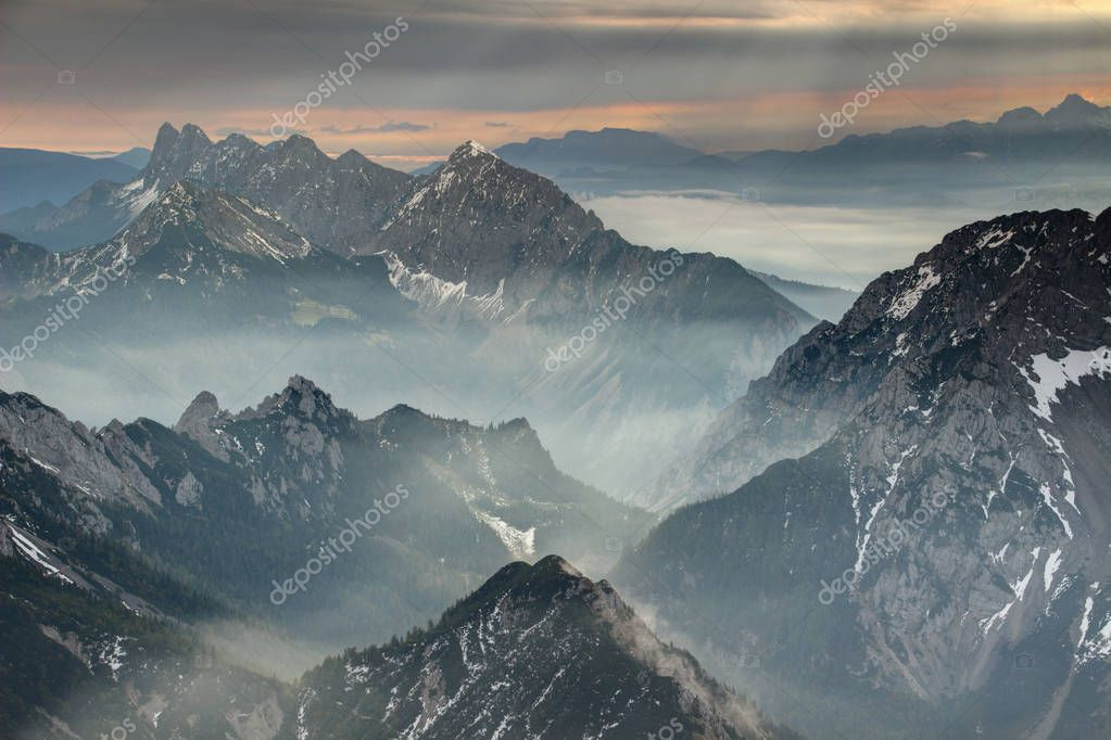 Sun rays burst through dark grey clouds over jagged hazy Koschutnikturm Kosutnikov Turn peaks of Koschuta Kosuta ridge in Karawanken Karavanke range in autumn morning, Austrian Slovenian border Europe