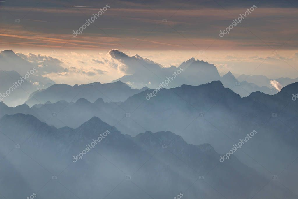 Clouds, Jof di Montasio and Fuart peaks rise above serrated blue ridges under  shining horizon in autumn lights, Triglav summit Triglav National Park Alpi Giulie Julijske Alpe Italy Slovenia Europe