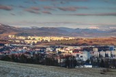 Fotografie Elevated view of socialist era tower blocks and houses in outskirts of Banska Bystrica with snow-capped Nizke Tatry mountain range in winter sunlight from Urpin hill Slovakia Central / Eastern Europe