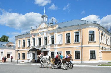 Kolomna. Russia, June, 29,2014, Russian scene: People in the wagon, drawn by the white horse rides near. the building of the former municipal Council along street Lazhechnikov (Kolomna city Council)