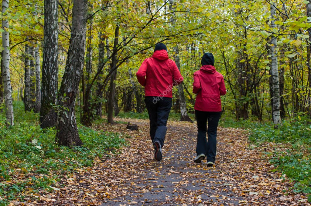 Two men in red jackets run through the autumn forest or park. Overcast weather. Autumn nature