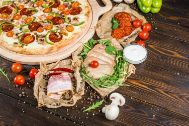 Large meat pizza with salami, bacon, mushrooms, tomatoes and paprika on a round cutting board on a dark wooden background. Ingredients.