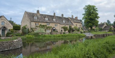 LOWER SLAUGHTER, COTSWOLDS, GLOUCESTERSHIRE, ENGLAND - MAY, 27 2018: Typical Cotswold cottages on the River Eye, Lower Slaughter, Gloucestershire, Cotswolds, England, UK