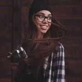 Mädchen mit Brille und Zahnspange mit Vintage-Kamera