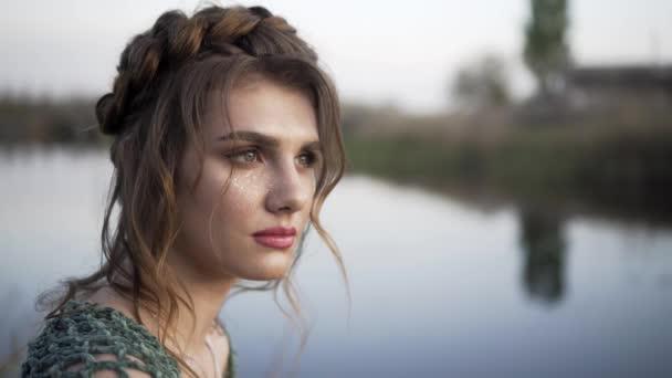 Fantasy dívka se těší lehký večerní vánek na klidném břehu jezera. Magické pohyby nevinných nymfa z divočiny