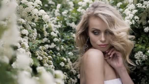 Divat fehér esküvői ruha, smink szőke menyasszony. Esküvő napján a menyasszony, menyasszonyi ruha. Nő szépségét és virágok. Szőke modell beltérben. Szépség portré, modell, a fehér menyasszonyi ruha