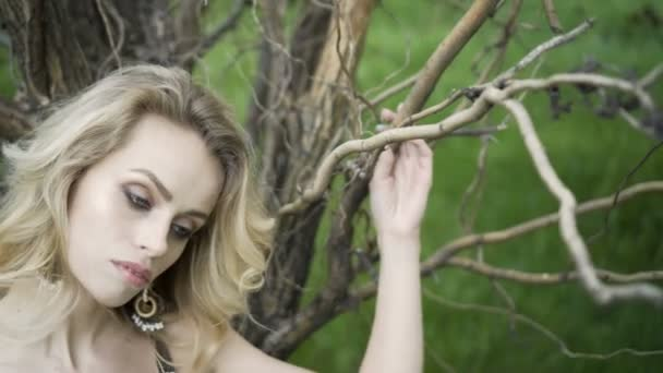Close up portrait of beautiful young woman hand through hair blowing in wind forest