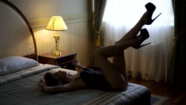 Vášnivé krásný model ležící na posteli v hotelu a pózuje pro fotografie