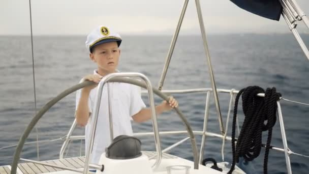 Litle children skipper at the helm controls of a sailing yacht during race.