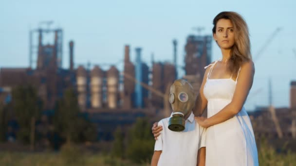 Mom And Son In A Gas Mask Stand In The Background Of A Factory And Smoking