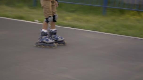 Rides roller skates. Boy rolls on rollers