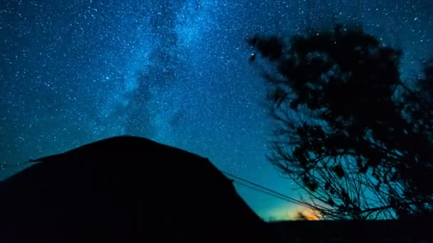 Sterne im Zeitraffer. Zelten unter den Sternen. Zeitraffer-Sterne bewegen sich über Bäume und Zelt