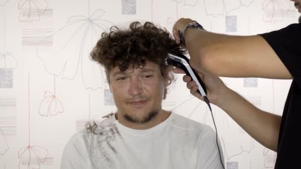 Mladý pohledný muž u holiče v moderním kadeřnictví