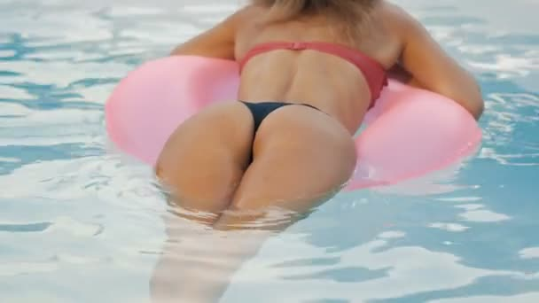 Dívka v bazénu plave na nafukovací koblihu růžové barvy