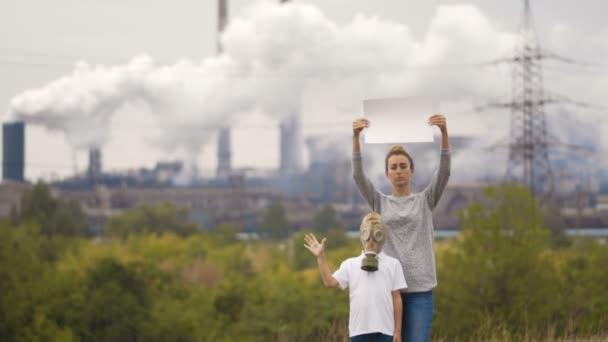 Mutter und Sohn in einer Gasmaske stehen im Hintergrund eine Fabrik und Pfeifen. In den Händen, mit einem Schild