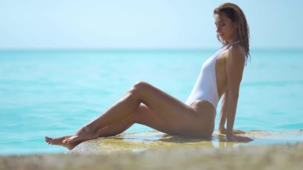 Fiatal szexi nő a bikini feküdt a homok és a tenger invitálja a vendégeket nyáron.