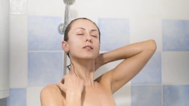 relaxační pod tekoucí vodou v horké sprše žena.