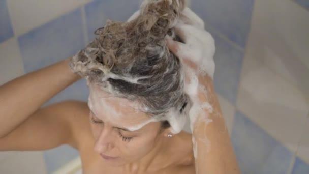 die junge Frau duscht und wäscht die Haare mit Shampoo.