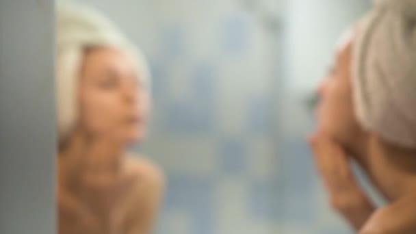 Dívka nátěry tvář s krémem po koupelně. Péče o pleť