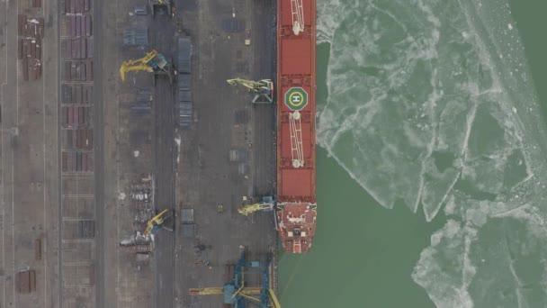Antenne 4k uhd Filmmaterial Frachtschiff mit funktionierender Kranbrücke in Werft für logistischen Import Export Hintergrund, Ansicht von oben