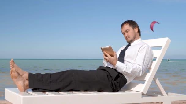 Fiatal üzletember dolgozik a strandon. Férfi profi ül a kényelmes nyugágyak