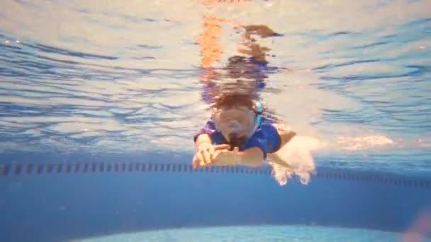 Unterwasser kleines Kind im Schwimmbad mit Maske