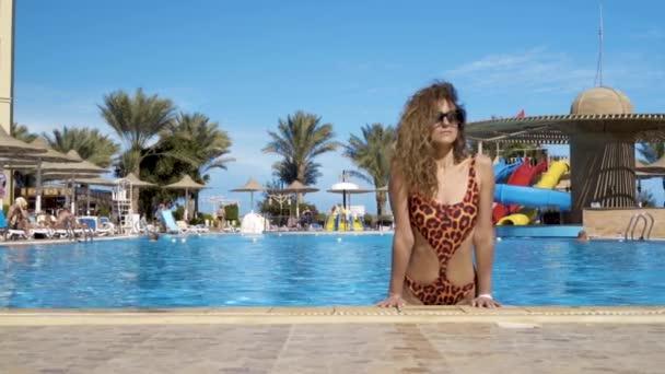 das Mädchen im Pool mit einem schönen Lächeln